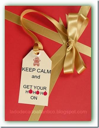 Imagem de um presente em papel vermelho amarrado um laço de fita dourada e uma Tag Keep Calm