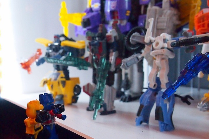 Optimus Prime and Bumblebee taking pictures of a toy display at Cybertron Con 2012