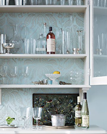 Give her bar a stylish update. Two disparate pieces -- a cabinet and a desk -- become one, thanks to the clever use of wallpaper. The sophisticated pattern makes a beautiful backdrop for a collection of glasses. To get this look, adhere a wallpaper panel above the desk and mount the cabinet. Remove cabinet shelves, and line the back with wallpaper; be sure to line up the center of the cabinet panel with the center of the wall panel below (marthastewart.com)