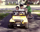 Kai and Eidan riding on the neighbor's battery powered mini Jeep