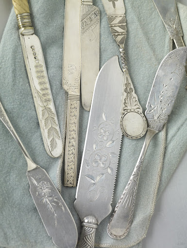 These butter and dessert knives, along with a large ice cream knife, center, represent a variety of styles, including delicate Japanese-inspired motifs, geometrics, and patterns that mix flowers, leaves and vines.