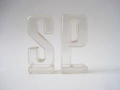 "Transparent salt and pepper shakers made in the shape of the letters ""S"" and ""P"""