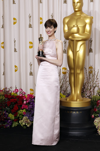 Anne Hathaway in Prada light pink duchesse satin backless column gown and Tiffany & Co. necklace.