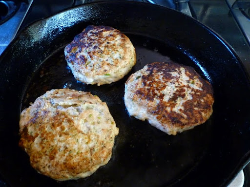 Salmon burgers ready to be removed from the pan.