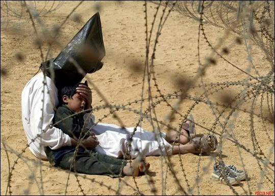 Hooded-Iraqi-prisoner-comforting-a-child-2003