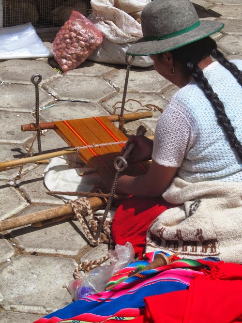 "A local women weaves on her ""telar"" staked between the cobbles"