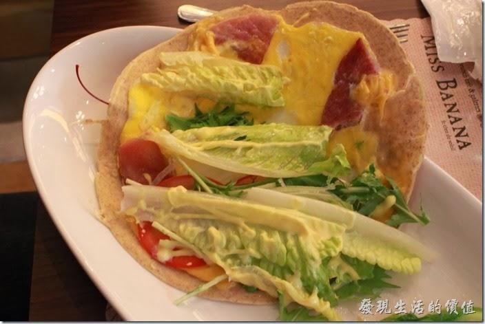 台南-巴娜娜早午茶趣。這份法式火腿乳酪薄餅裡頭包有火腿、乳酪、羅勒、番茄、煎蛋、酸黃瓜及其他佐料,稍為有一點點墨西哥捲餅的口感。這種法式薄餅的餅皮是軟的,所以不太能整個拿起來吃,必須用刀子切成一片片的食用,稍為給它麻煩。