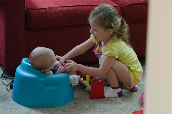 Sam trying to get Nate to play with her toys