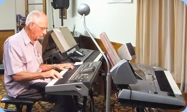 John Perkin playing his Korg Pa3X amidst an array of keyboards setup for the eveings entertainment. Photo courtesy of Dennis Lyons.