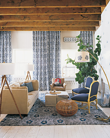 Rebecca's living room is another example of the proper way to use pattern. The monochromatic color scheme keeps things calm even though there is a great deal of pattern. A graphic damask fabric was used for the floor-to-ceiling curtains in the living area. The floral rug is by British designer Neisha Crosland.