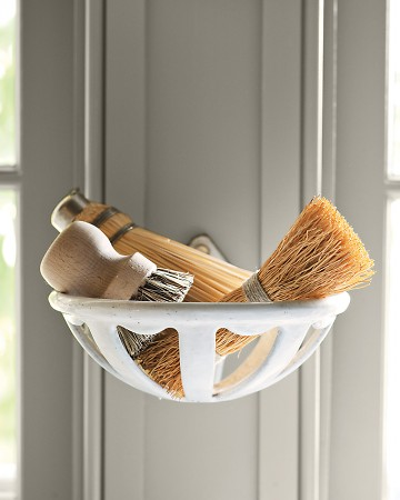Martha collects vintage enamel holders, originally used for soap and sponges in bathrooms. She mounts them by sinks to hold sponges, brushes, and scrubbers.
