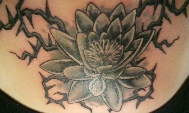 black and grey lotus flower chest tattoo