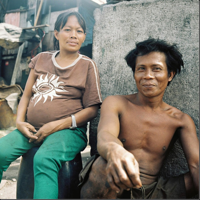 "A couple expecting a child rests outside their house in Happyland, a large garbage dump in Manila. The place and its adjacent poverty-stricken areas are also fondly called ""children factory"" due to the sheer number of children and pregnant women living in the community."