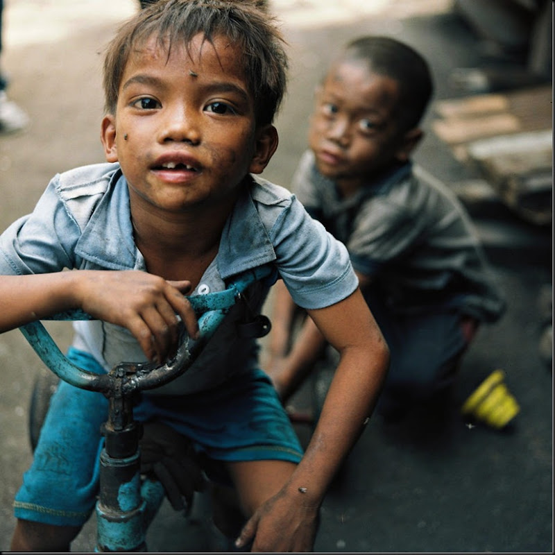 "Children of residents of Happyland play on an old, discarded bicycle. Happyland is a large garbage dump in Manila where families of scavengers and charcoal-makers call the place home. The place and its adjacent poverty-stricken areas are also fondly called ""children factory"" due to the sheer number of children and pregnant women living in the community."
