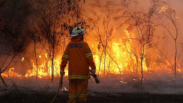 An Australian firefighter faces a bushfire. Jonathan Carroll