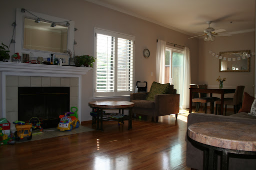 Open living area with hardwood floor and a cute fireplace. Plantation shutter is throughout the house.