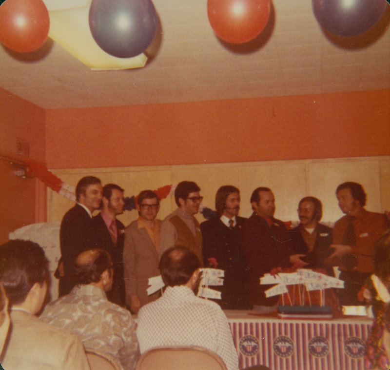 The First Annual Meeting of Dignity is held in Los Angeles. Seventy-four members attend the potluck dinner/election including 22 priests. Included in this image are (left to right) Bob Mitchell, Rod Flewelling, unknown, unknown, Bob Fournier, unknown, Joe Killian, and unknown. February 19, 1972.
