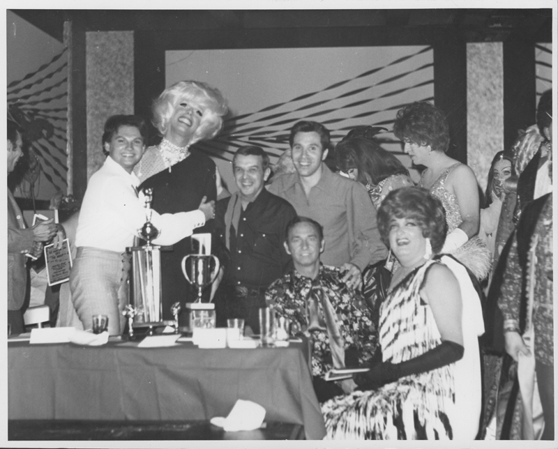 Party at  Patch 2  in Hollywood (fromerly Ciro's). From left to right: Jim Bailey, Roby Gaynor (as Carol Channing), Dick Michaels (Advocate editor), Reverend Pat Rocco, Ray Harrison (sitting, Gay Girls Riding Club), and Warren Fremming (as Freida). 1969.