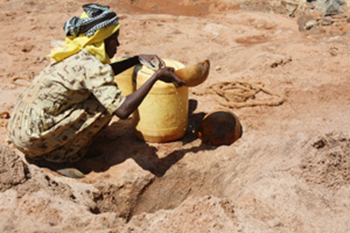 In southern Kenya, a woman uses a gourd to scoop water from a dry riverbed. During droughts, many women walk hours to find water. Photo: Laura Sheahen / Caritas