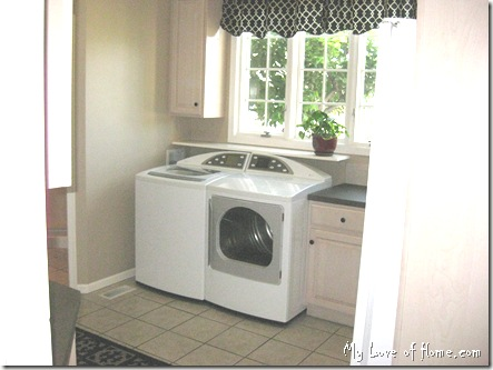 white washer dryer, beigh tile, beige walls, white wood work, black curtains, red pot