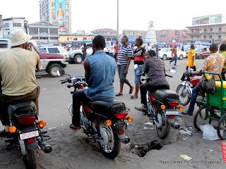 Place des artistes, Rond-point  victoire/ Kinshasa. Le trafic routier  n'est pas intense ce 2/06/2011. Quelques motards discutent en attendant l'arrivée des passagers. Ici, comme dans d'autres carrefours, les motos qui font le taxi n'ont pas toutes des plaques d'immatriculation. Ce qui n'empêche pas les motards d'exercer leur activité.