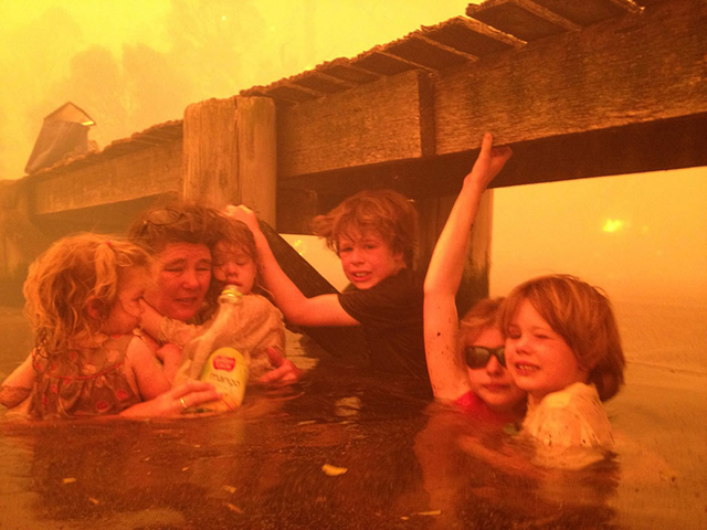 A Tasmanian family takes refuge from record wildfires in the seawater under a jetty, 8 January 2013. Tammy Holmes (second from left) and her grandchildren, (from left) Charlotte, Esther, Liam, Matilda, and Caleb, survived the bushfires that raged for three hours. Photo: Tim Holmes / AP