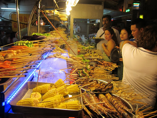 A hawker stall's huge array of meats and vegetables ready for the grill.