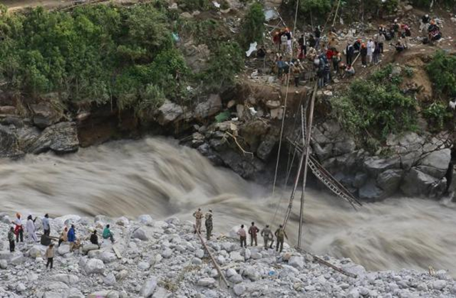 Soldiers try to repair a temporary footbridge over River Alaknanda after it was destroyed, during rescue operations in Govindghat in the Himalayan state of Uttarakhand, 22 June 2013. Early monsoon rains have swollen the Ganges, India's longest river, swept away houses, killed at least 138 people and left tens of thousands stranded, local newspapers reported. Photo: Danish Siddiqui / REUTERS