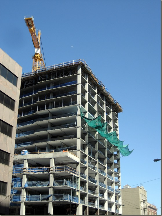 moon over building, crane, green netting