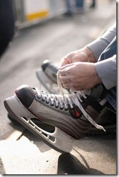 tying-laces-of-ice-hockey-skates-at-skating-rink