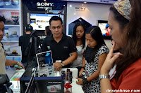 Bloggers and walk-in customers ask the salesperson about the new Sony Handycam with built-in projector