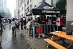 An afternoon rainshower wasn't enough to keep thousands of New Yorkers from chowing down at the BBQ Party, but it did inspire some huddled masses to form under every available tent.