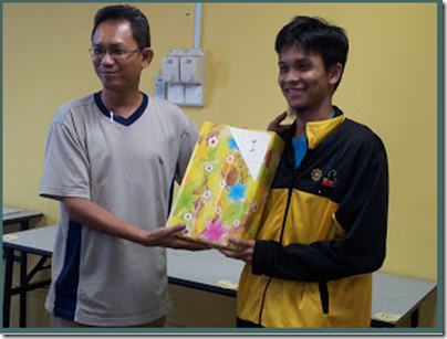 Nik Ahmad Farouqi receiving his Champion's prize from the sponsors.