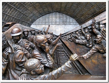 A statue depicting St Pancras station over the decades. The troops departing while injured comrades return.