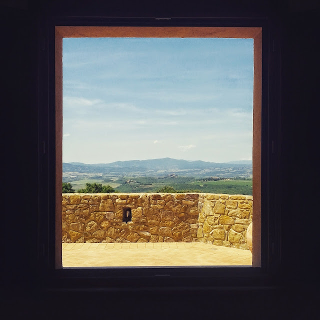 Tuscan landscape seen through the window of a Montalcino winery