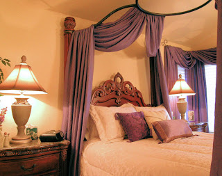 Beautiful lamps with hand-painted shades cast soft lighting in this romantic bedroom.
