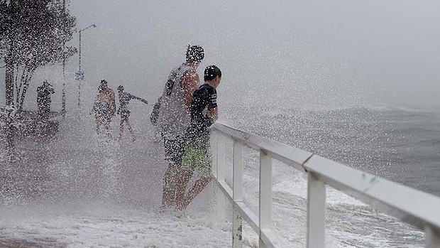 Waves break over onlookers at Shorncliffe, a Brisbane suburb, 27 January 2013. The heavy rainfall following cyclone Oswald which caused widespread flooding in Queensland is hit Sydney on Monday, 28 January 2013. Photo: Michelle Smith / Sydney Morning Herald