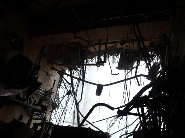 A large hole blasted in the south-side wall of the 4th floor of the Fukushima nuclear power plant Unit 4 building, 10 June 2011. The hole was caused by the March 15th explosion. The mangled piping is necessary to restore cooling to the spent fuel pool. TEPCO