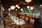 The indoor-outdoor restaurant has teak furniture and beamed ceilings. The green centerpieces stand out on the white table runners.