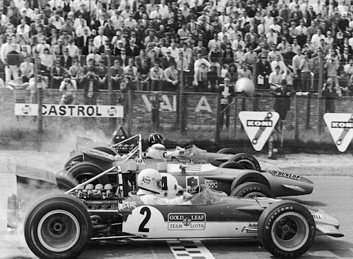 Jochen Rindt (AT, Lotus 49), eventual winner Jackie Stewart (GB, Matra MS80) and Graham Hill (GB, Lotus 49) wheelspin away from the start of the 1969 Dutch GP at Zandvoort. The side of Rindt's helmet bears the legend 'This $pace to let' which was put there by his manager, one Bernie Ecclestone.... . Dutch Grand Prix, Zandvoort, 1969 Formula One World Championship.