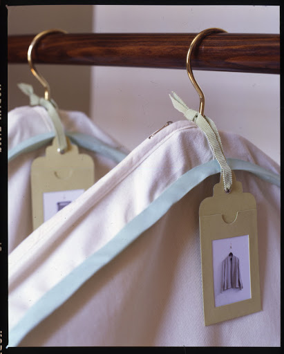 To quickly see what's inside a canvas garment bag, tie tags with cut out windows around the hook of the hanger, then slide in a digital image of the garment stored inside.