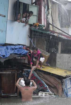 A man gives food to people staying in flooded homes in Quezon City, north of Manila, Philippines, on 7 August 2012. Emergency crews were scrambling to evacuate tens of thousands of residents. Associated Press
