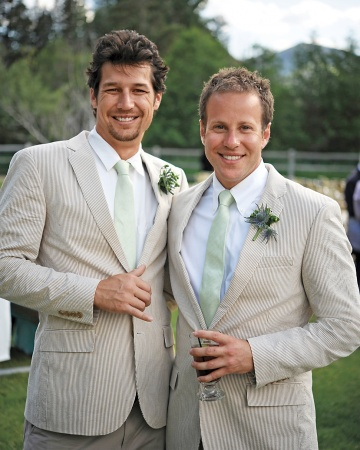 A pair of groomsmen mug for the camera in suave striped suits. Groom Peter gave them all custom Nike sneakers that sported the wedding date and each man's last name.