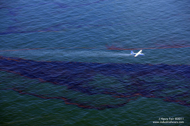 A quad-engine plane applies dispersant on the oil slick at the BP Deepwater Horizon spill site. In spite of an EPA directive to cease the application of dispersants, BP continued to spray aerially and inject them at the well. J. Henry Fair / industrialscars.com