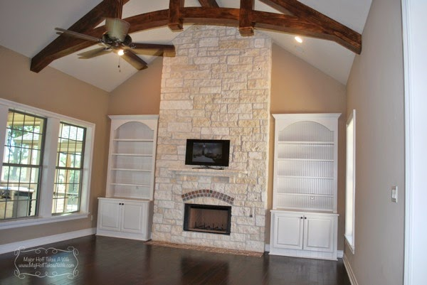 White beadboard bookcase cabinets flanking austin stone full fireplace