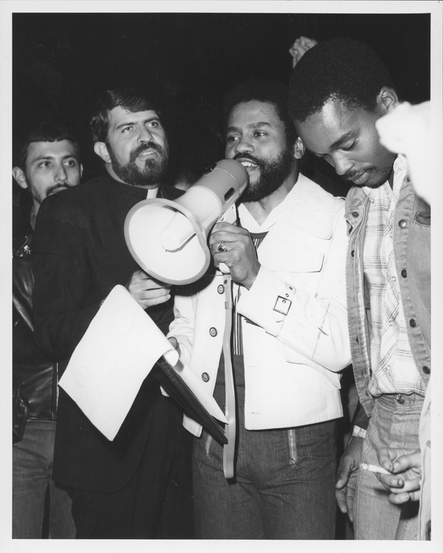 Ron Grayson speaks out next to Reverend Troy Perry at a protest against the Los Angeles Police Department and police chief Ed Davis. 1975.