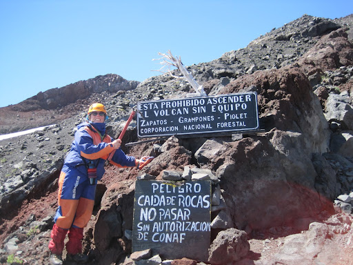 Signs on Volcan Villarrica pointing out the required equipment and warning about falling rocks.