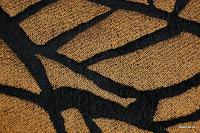 Tkanina obiciowa z efektem metalicznym. Motyw roślinny - liście. Czarna, miedziana.