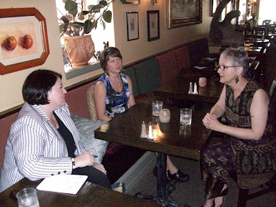 Tsalika Drown and Lorraine Williams from Cafe Dodici talk with Alison Hart, an Aide from Senator Tom Harkin's Office