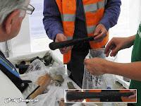 Een zeer interessante bewerkte houten pen, vermoedelijk uit de 13e eeuw, wordt nat gehouden in een plastic zak met water.